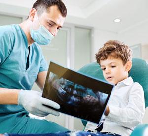 Zahnarzt erklärt Kind die Behandlung